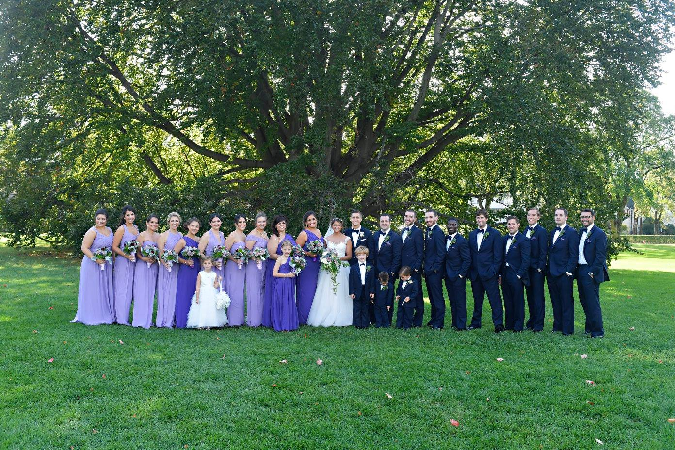 bridesmaids in mismatched purple gowns and groomsmen in black tuxedos