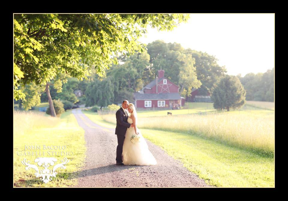 bride and groom outside by barn