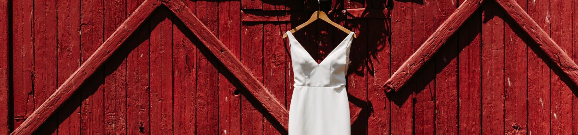 red barn door with hanging white wedding dress