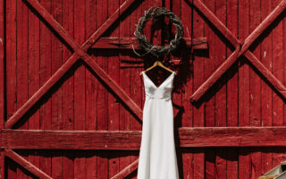 red barn door with hanging white wedding dress