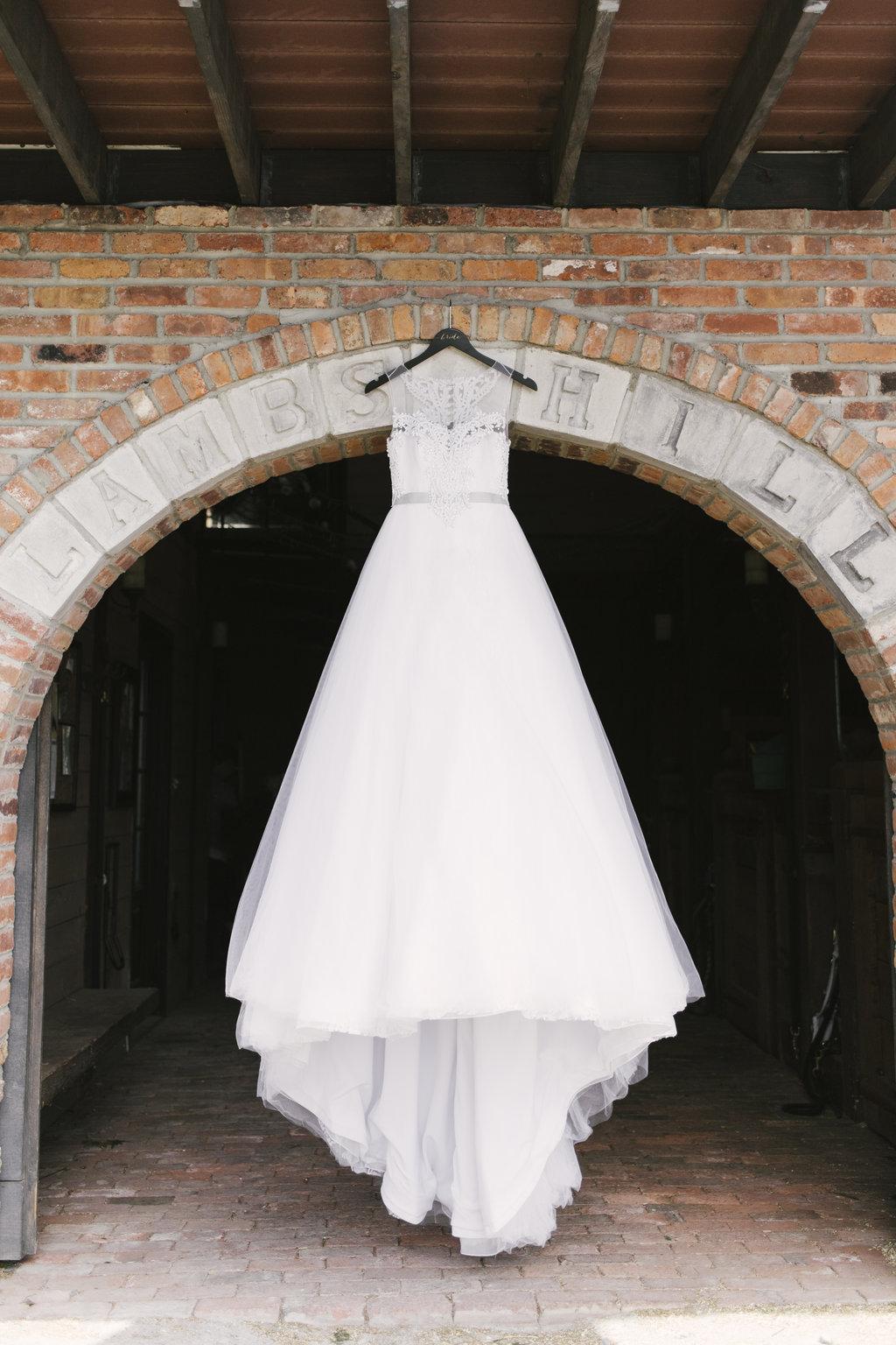 wedding gown hanging in doorframe
