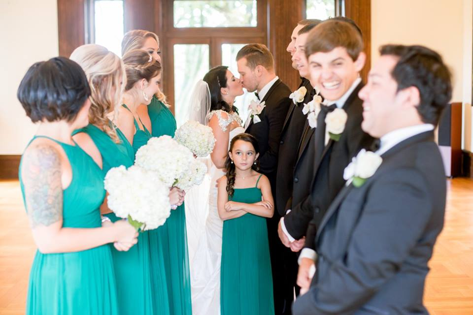 wedding party looking at bride and groom kissing