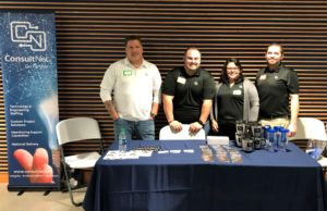 Team standing behind table and ConsultNet sign at Google DevFest 2018