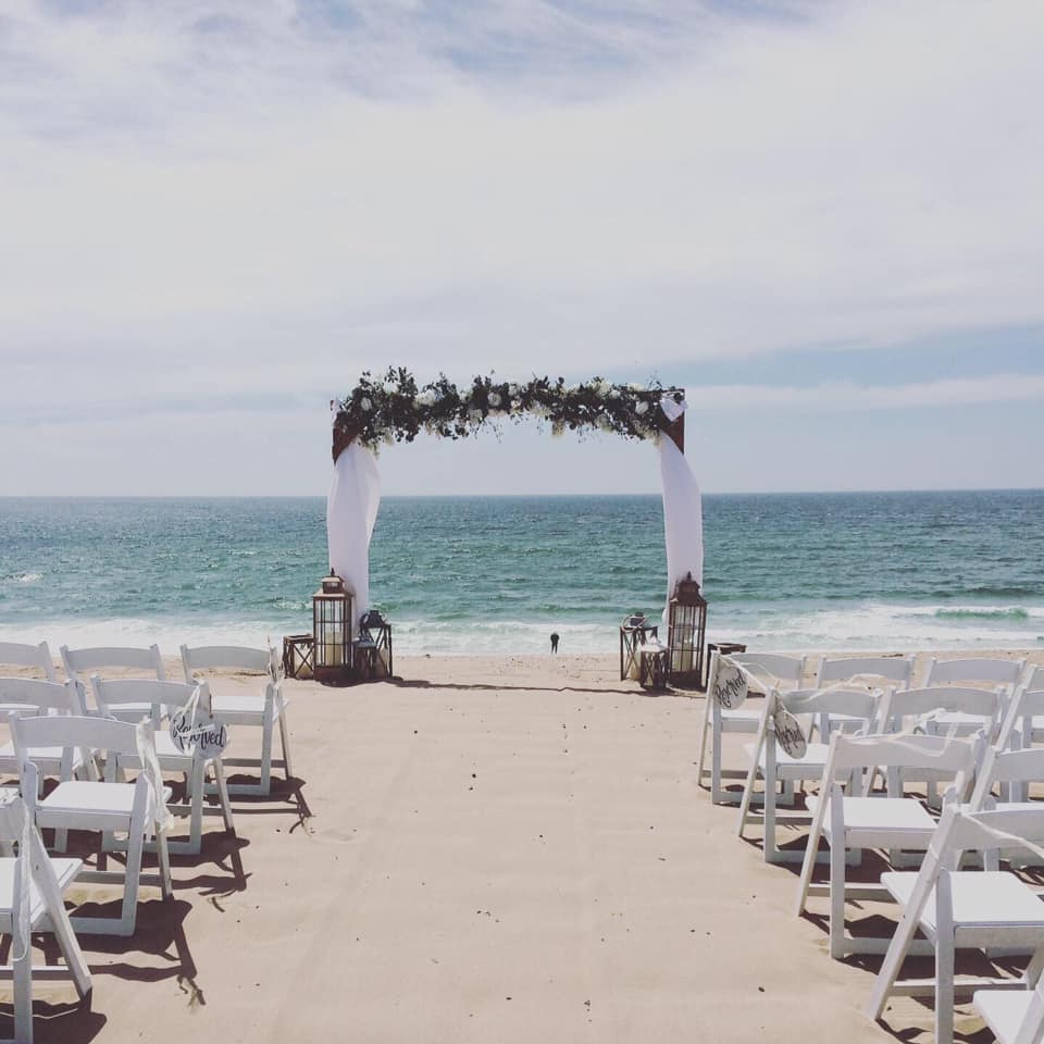beach wedding ceremony arbor with florals and lanterns