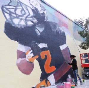 Reggie O'Neal, also known as L.E.O. works on his mural, a tribute to slain teenager Richard Hallman on the Looseys wall.