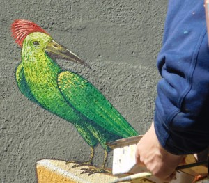 Aleksei Bordusov adds a tropical bird to the mural on the final day.