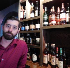 Bartender Jim Asp and some of Sidecars whiskeys.