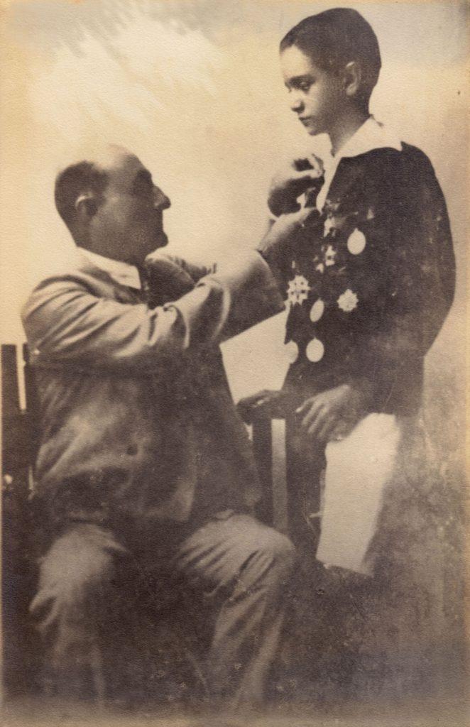 1929. Octubre, 10. Premiación de fin de curso en el Colegio San Ignacio, batiendo récord al conseguir 15 medallas en su pecho. Aparece con su padre adoptivo el Dr. Tomás Liscano.