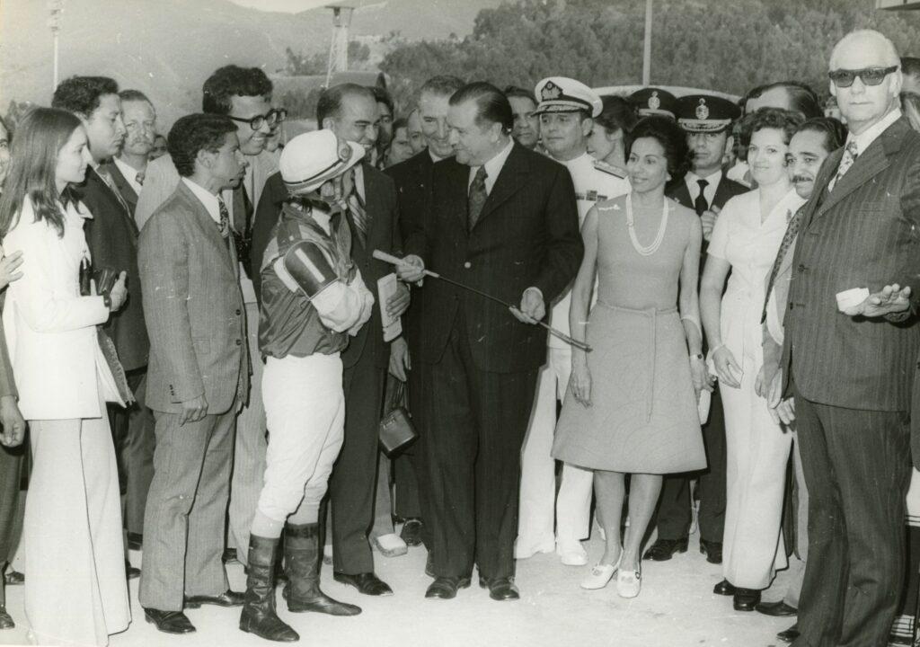 1973. Abril, 19. En el óvalo de ganadores, Hipódromo La Rinconada, recibe como obsequio el fuete del jinete Gustavo Ávila, en el Clásico Presidente de la República.
