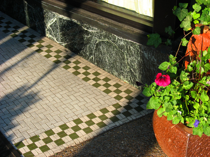 The basket weave field with a checkerboard border backed up by a nice piece of serpentine marble make for a very attractive entryway.