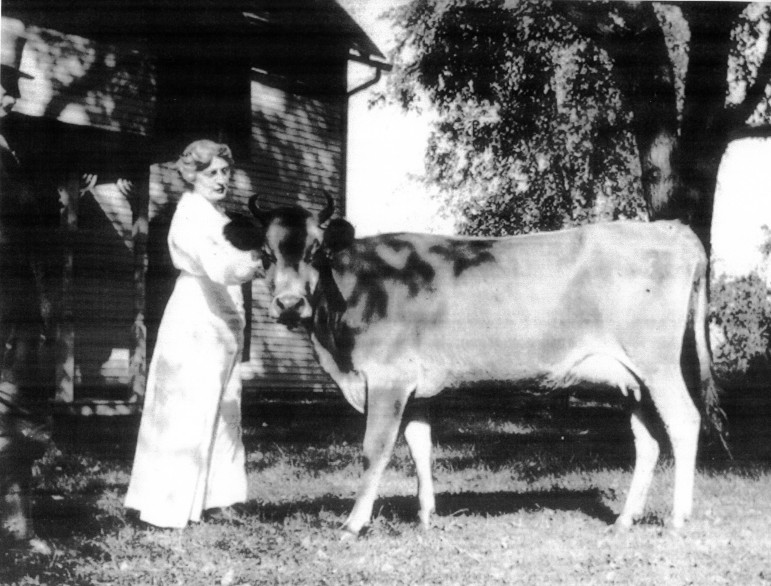 Edward (standing at left) and Elinor with a highly regarded animal.  In the front yard at Woodside in 1918.