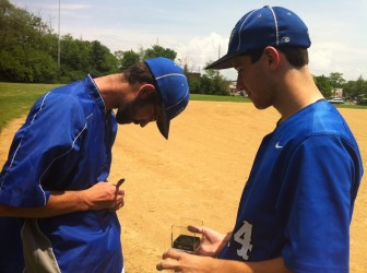 Coach Jonathan Webb signs a game ball given to him by senior Rich Rasmussen.