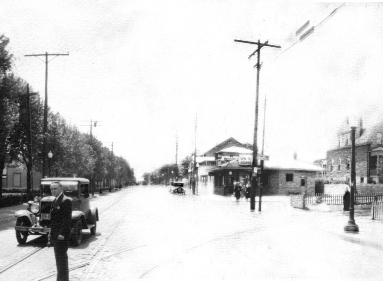 The seventh and last section is looking south on Sutton.  the same house is visible at each end of the photograph.  The building advertises Barbe-Q. It is now home to Krodinger Realty.  The brick barbecue pit cna still be seen along the sidewalk sans chimney.  Regular viewers of this space may remeber that harper's Pharmacy gradually morphed into a full time camera store.  I suspect this photographer (possibly salesman) may have been demonstrating equipment to the Harpers.  If you have a better theory, let's hear it.
