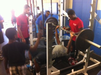 Romelle Person spots for Jordan Goliday in the MRH weight room. Darren Williams waits his turn.