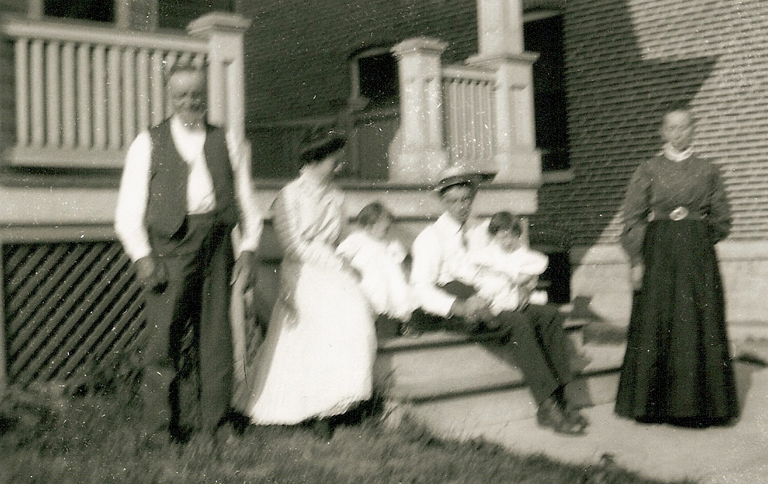 The whole family on the front porch but now the four family building next door has been constructed.