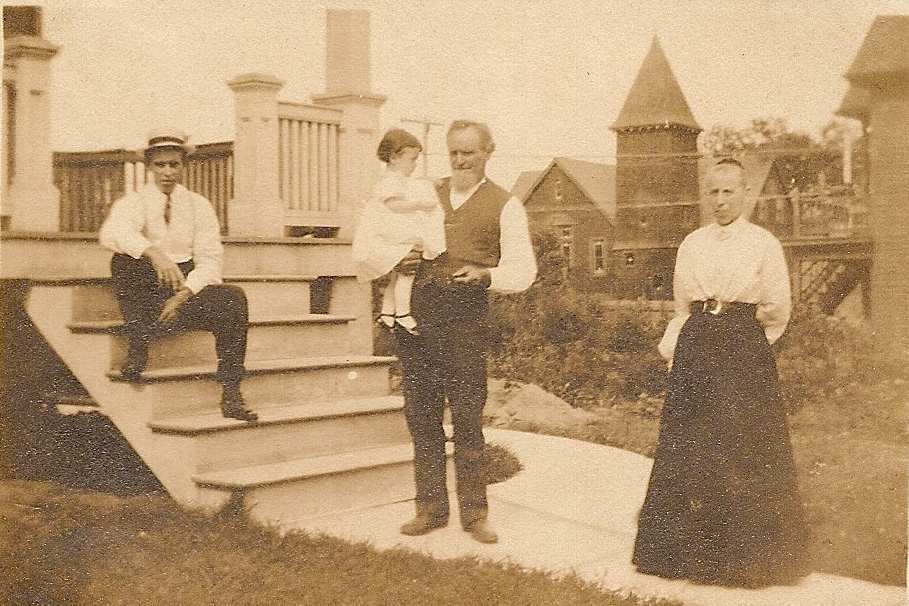 Standing in front of their home at 7415 Hazel are John and Minnie (nicknamed Mina) Zimmerman.  John is holding a grandaughter, either Opal born 1906 or Lorine born 1908.  They are the children of John O. who is seated on the steps.