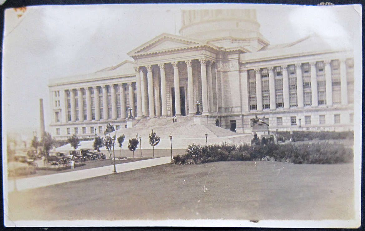 Since this photo is part of the same group I assume the building is the state capitol of Illinois.  I have reason to believe that the small white figure by the cars is Marjorie.