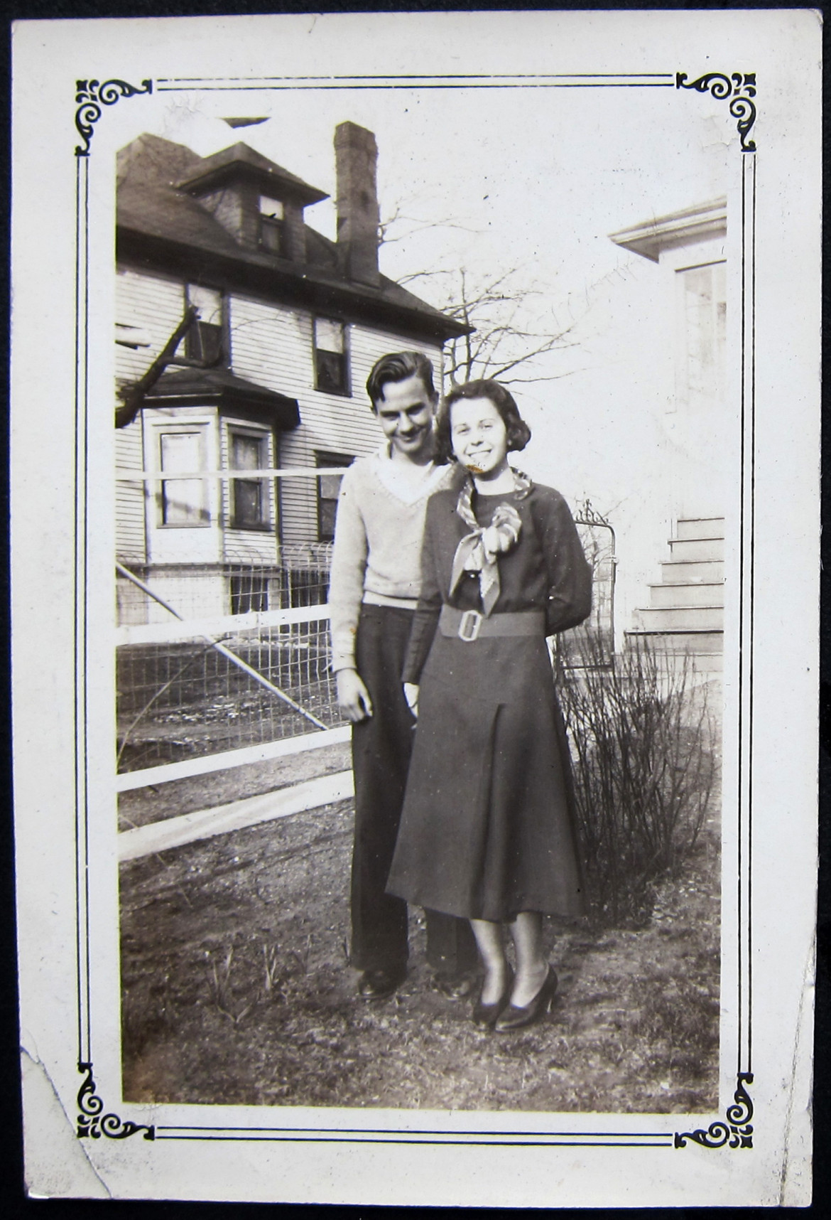 Marjorie with an unidentified friend with the neighbor's home in the rear.