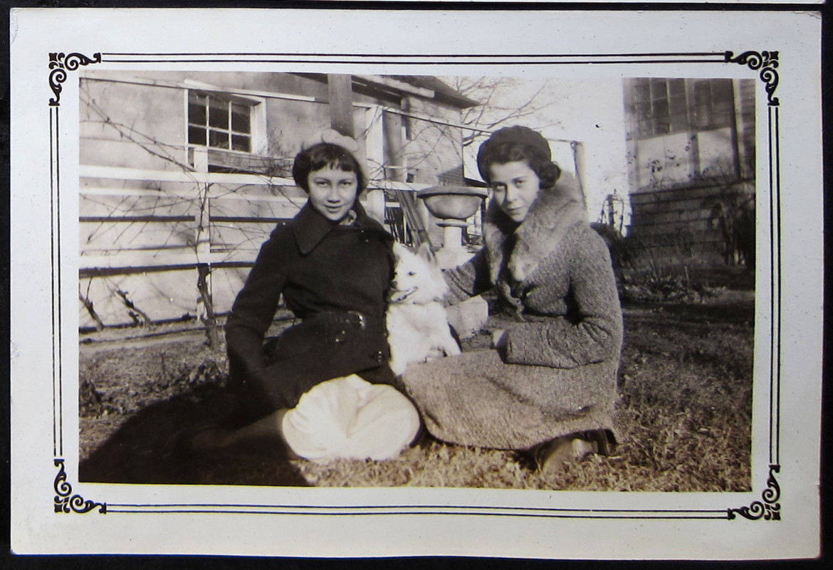 In the backyard at home with her white dog and an unidentified friend.