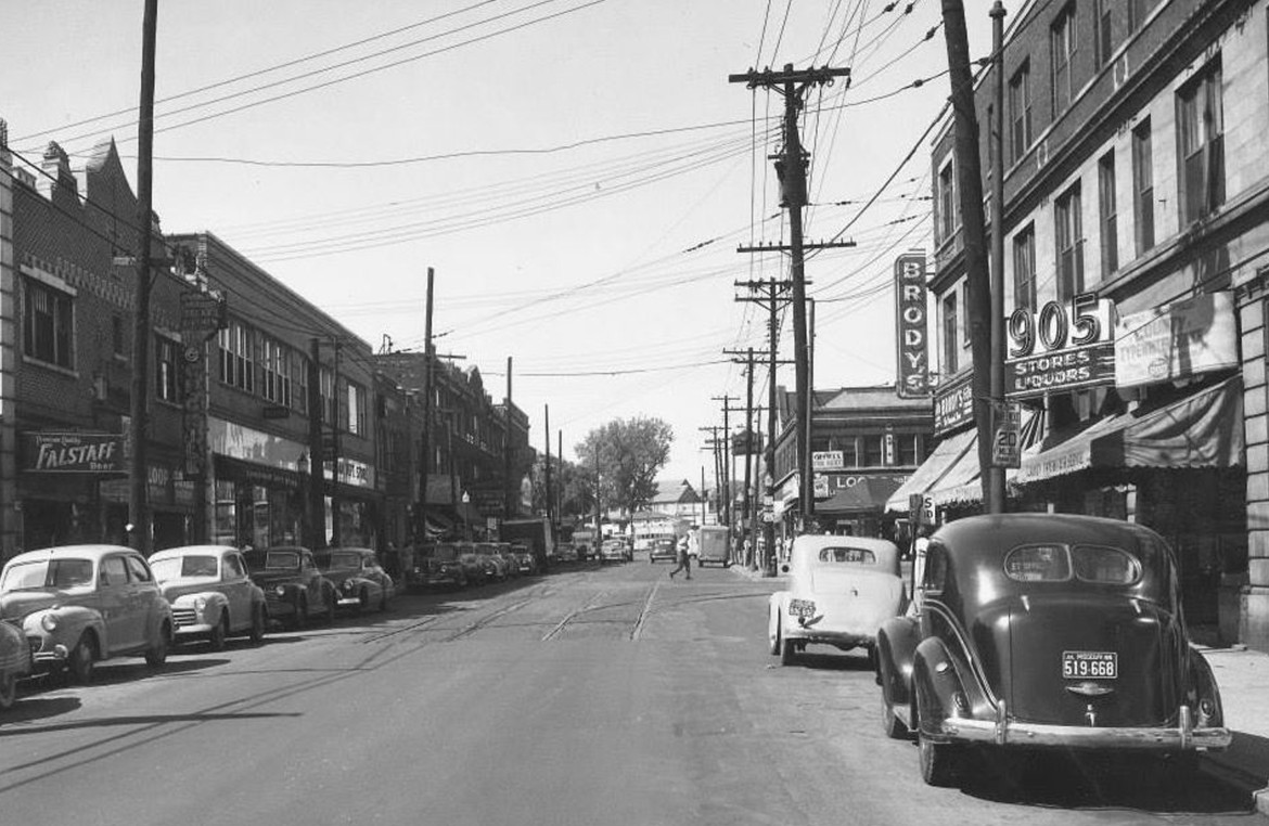 The location of this 1949 image is the 7100 block of Manchester looking west. The streetcar tracks are being paved over. The Maplewood theater is visible on the left.