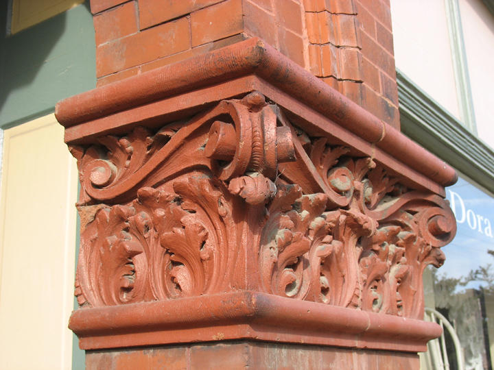 The capital on this brick pillar is an example of some of the finest terra cotta in Maplewood. The pillar supports a brick arch over the entrys to the second floor apartments. The arch has a limestone keystone. The design of the capital looks like acanthus leaves topped with scroll work. Two architectural motifs that are positively ancient. Look closely at the top and bottom half round moldings. You can see the lines of a rake, a common clay tool that a worker used to score the clay in order to give it more texture.