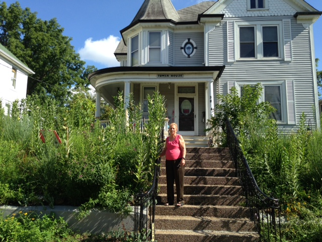 Alice Hezel at her house on Cambridge, surrounded by Milkweed plants and others.