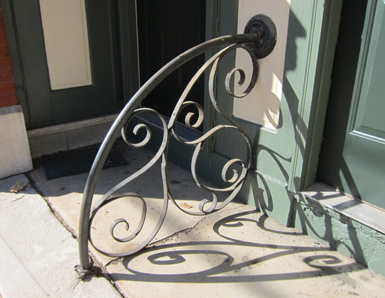 A great little wrought iron railing between the two doors to the upstairs apartments.