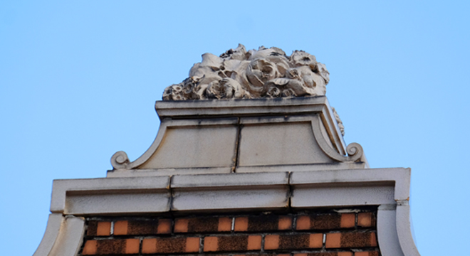 I think these must be terra cotta flowers sitting on the parapet coping.