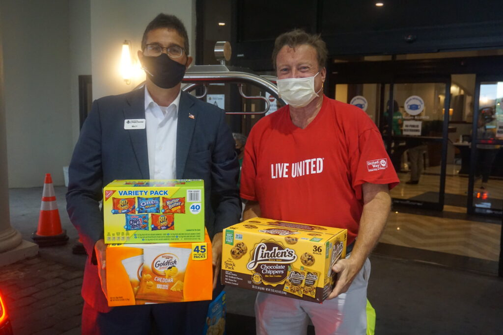 United Way of Delaware's Tim Sheldon carrying donated snacks with New Castle County Executive Matt Meyer