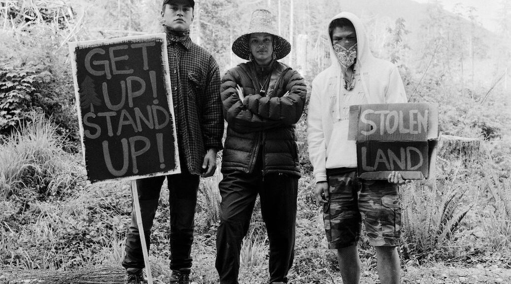 Patrick Jones, Aya Clappis and Victor Peter stand together at the Fairy Creek blockade headquarters