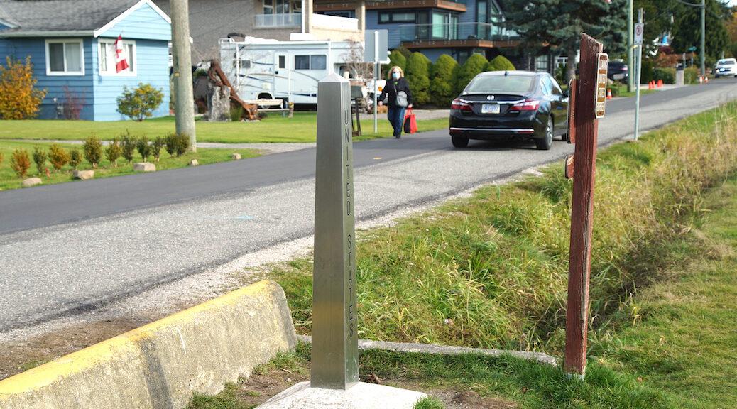 woman walking beside narrow ditch that divides Canada from the US in BC
