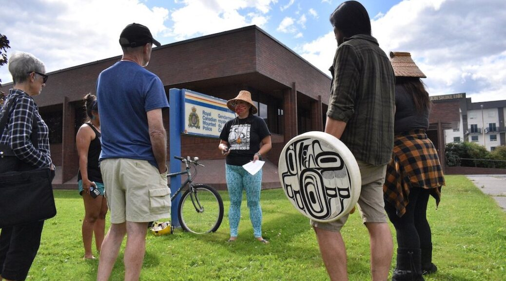 A group five Indigenous women and a man gather in a circle outside the Terrace RCMP station