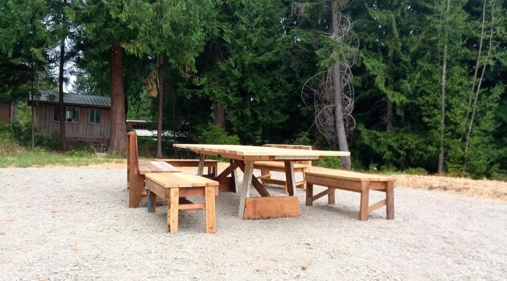 A table and benches sitting in a gravel clearing