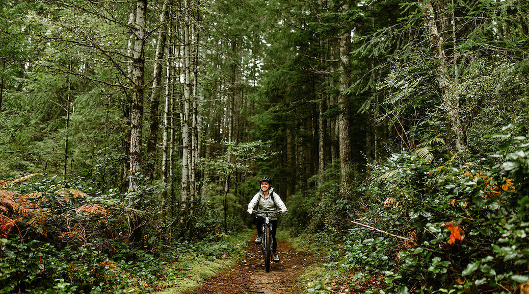 Woman cycling through the forest on one of Cortes Island's trails