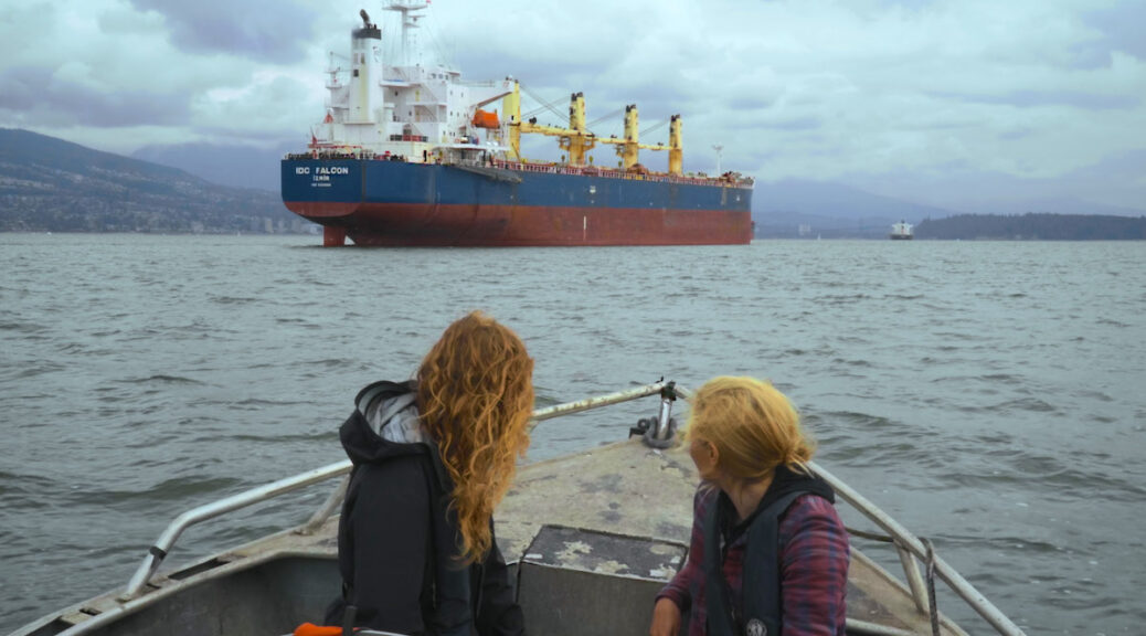 Two women in a boat looking at a nearby oil tanker