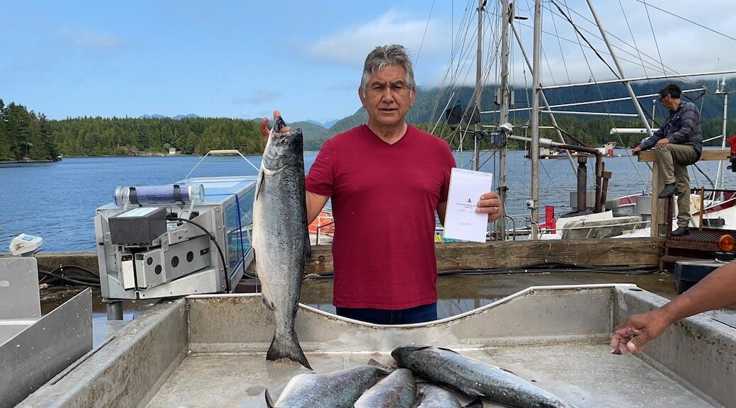 First Nations man holds up salmon