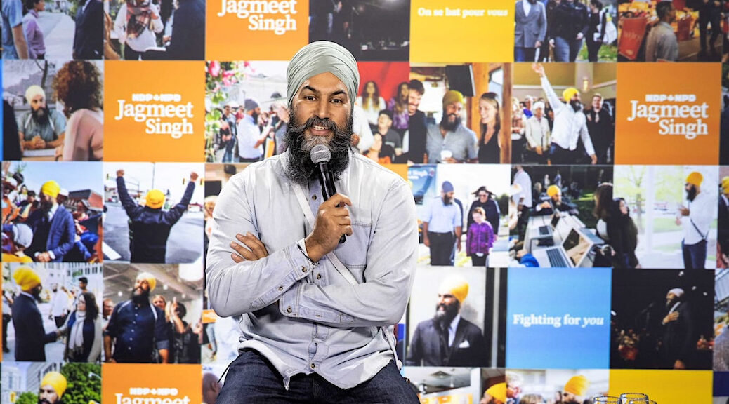 Jagmeet Singh speaking into a microphone, and sitting in fron t of a collage of NDP posters