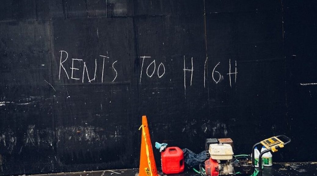 A dark wall with the words 'Rents too high' written on it.