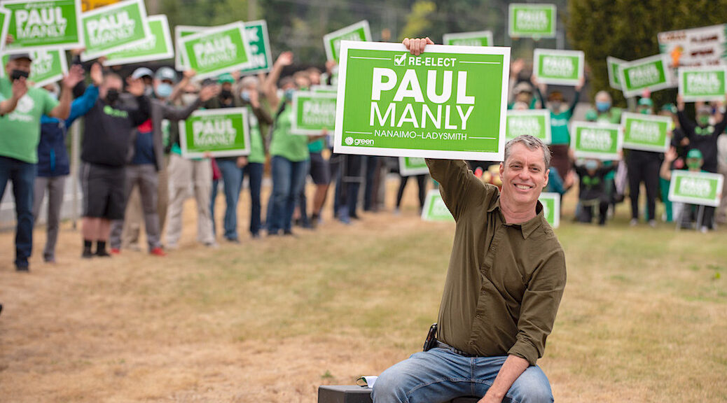 Green Party MP Paul Manly sitting in a field, a crowd carrying 'Paul Manly' posters is behind him s