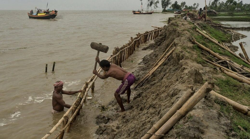 Two men building up a dike. The setting is tropical