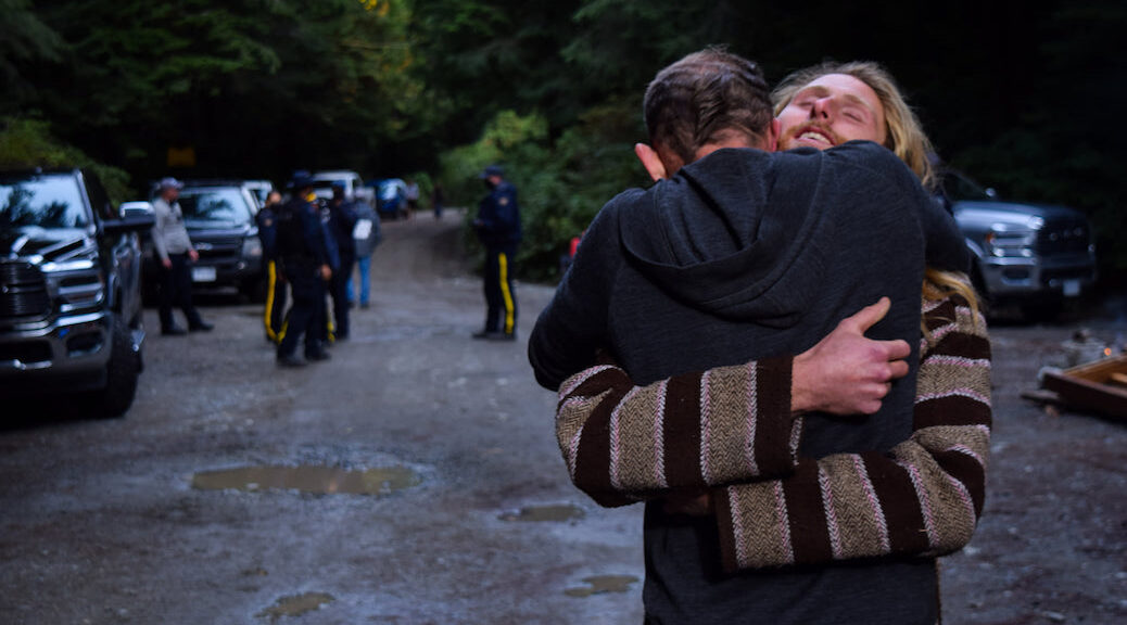 Two forest defenders embrace, as police look on