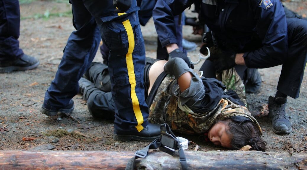Two police offiucers handcuffing an unconscious Indigenous woman