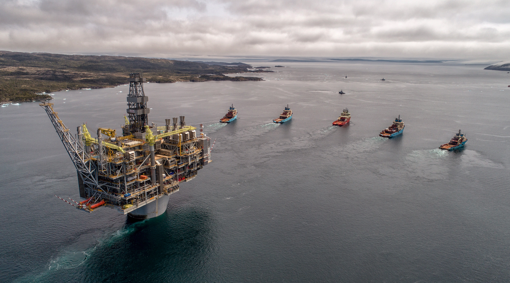 An oil platform being towed by five tugboats
