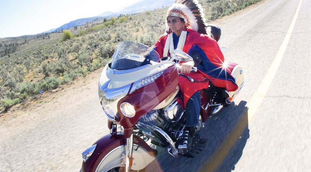 First Nations man wearing eagle headdress on a motorcycle