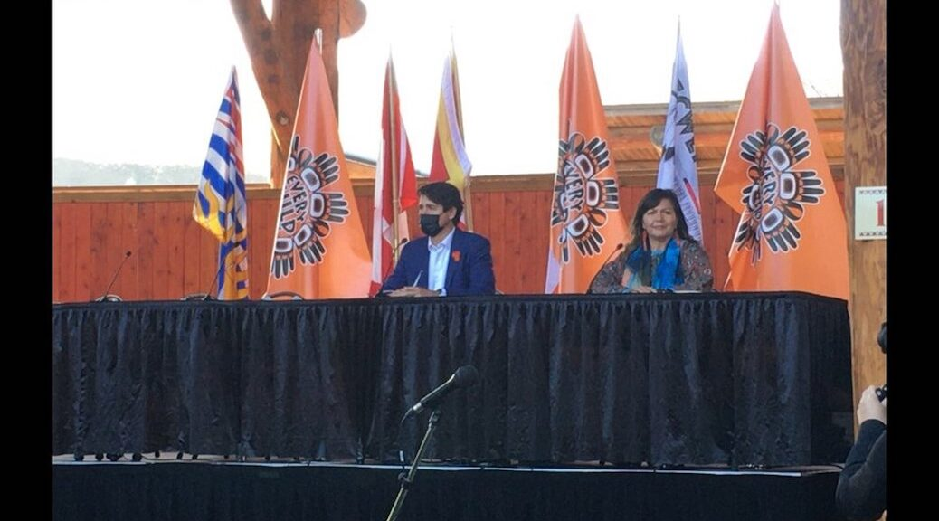 A masked Caucasian man and unmasked Indigenous woman sit at a table, addressing the press