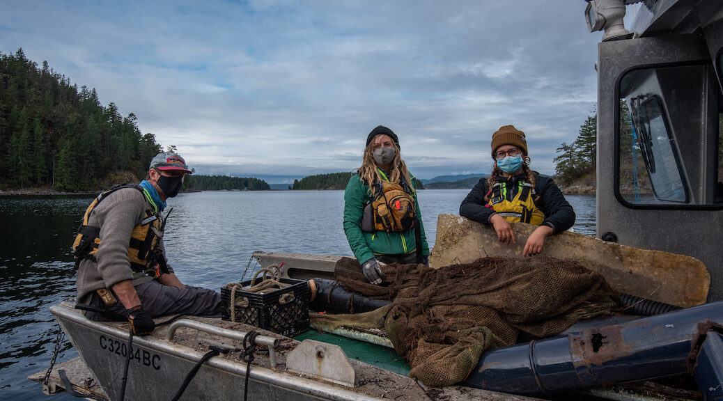 Three youth, all wearing masks and raingear, in a barge full of debris.