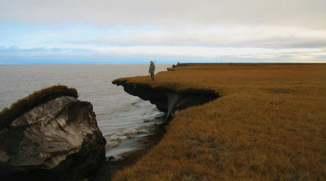 man standing near the edge of a cliff, part of which has dropped into the ocean