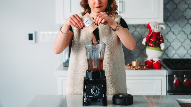 woman mixing a supplement into a blender