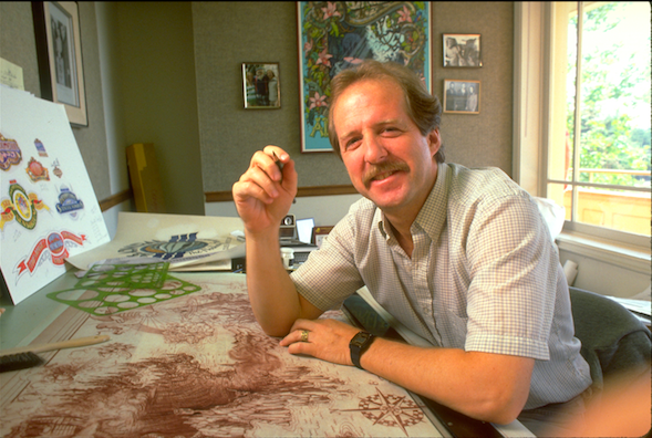 James Michaelson, graphic designer and one of the key show designers for the overall project, is seen at this desk at Landmark Entertainment.  On the wall behind him is one his famous DISNEYLAND ATTRACTION POSTERS (The Jungle Cruise), and to his right are some of the initial logo designs that he created for the many shops, stores and attractions within the Power Plant. Copyright The Goddard Group All Rights Reserved