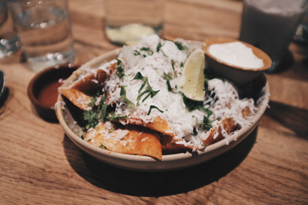 totopos con chili - tortilla chips, salsa de arbol, cotija cheese, onions, cilantro, crema and lime